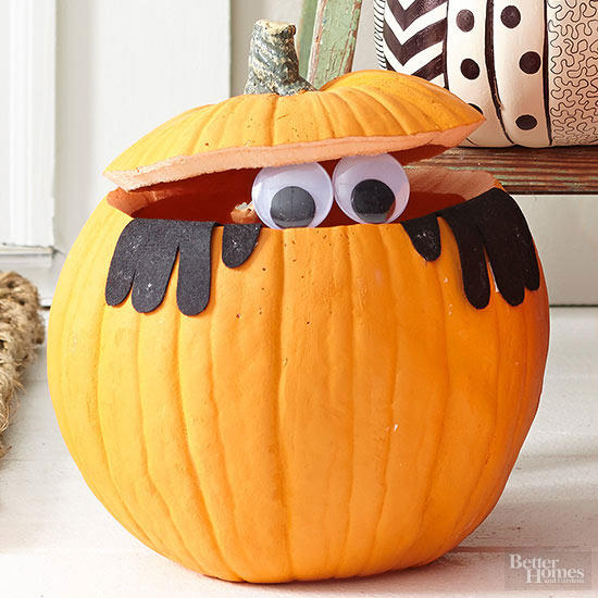 "It's hard to tell, but it sure looks like someone's eyeing your candy bowl. This black-gloved pumpkin dweller is biding his time before popping up and yelling ""Boo!"" or stealing a few handfuls of candy. Once the kids take a closer look at him, we're guessing he'll steal a few giggles, too."
