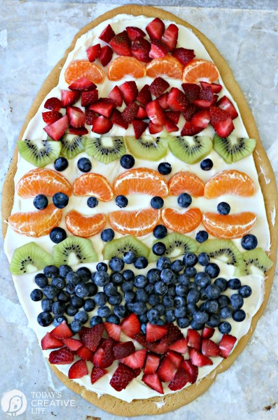Sugar Cookie Easter Egg Fruit Pizza - Easy to make Easter treat. Cream Cheese frosting topped with your favorite fruits