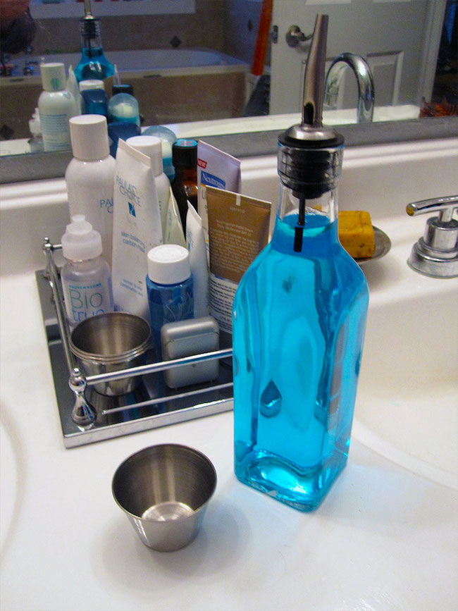 Use olive oil and vinegar bottles to store ugly mouthwash containers