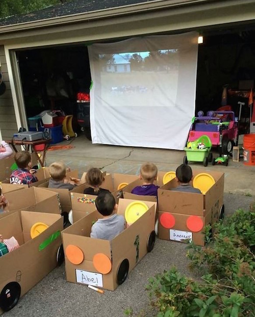 "Drive-In Movie for kids. Perfect for warm summer nights. Each kid decorates their ""car"" made out of cardboard boxes. Movies are projected on a white sheet out of a garage. FUN!"