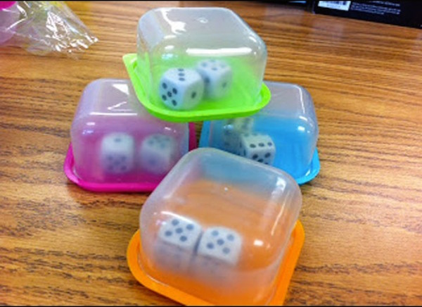 Playing an educational game that includes dice at school or for homework? Put them in small plastic containers. When they roll, they stay together and don't make as much noise. Brilliant!