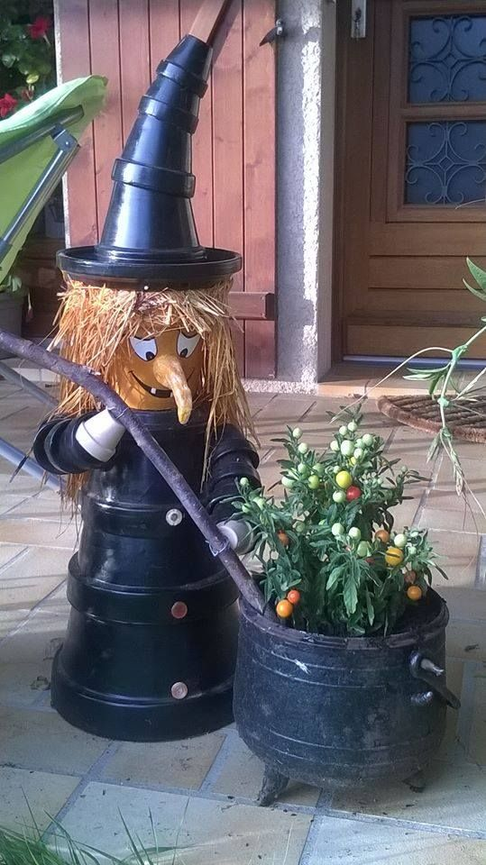 IY terra cotta pot witch! Made by painting pots black and stacking them. The witches caldron is actually a plant! So smart and creative!