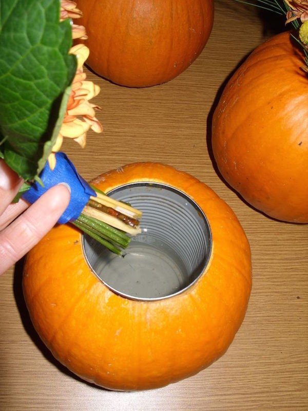 Carve out the center of a pumpkin, insert a soup can, and place flowers inside for an expensive looking (yet cheap) DIY fall centerpiece.