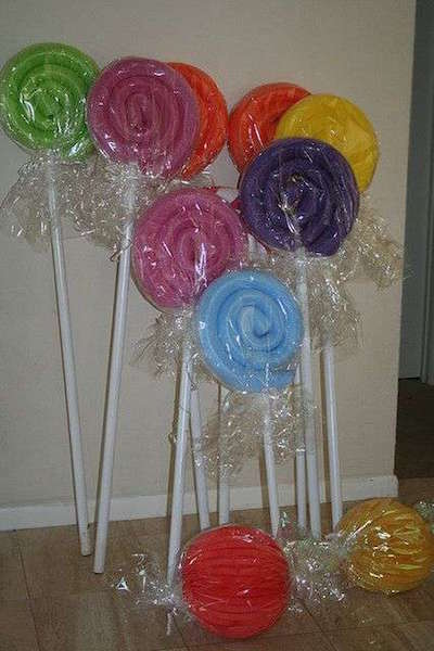 Make GIANT lollipops using pool noodles, cellophane, and painted dowels or pvc pipe! Use a heavy duty hot glue to roll the lollipops into a candy shape. So smart!