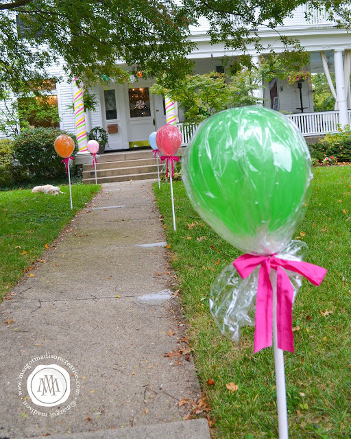 Balloons wrapped in cello and tied to white painted dowels - great idea!