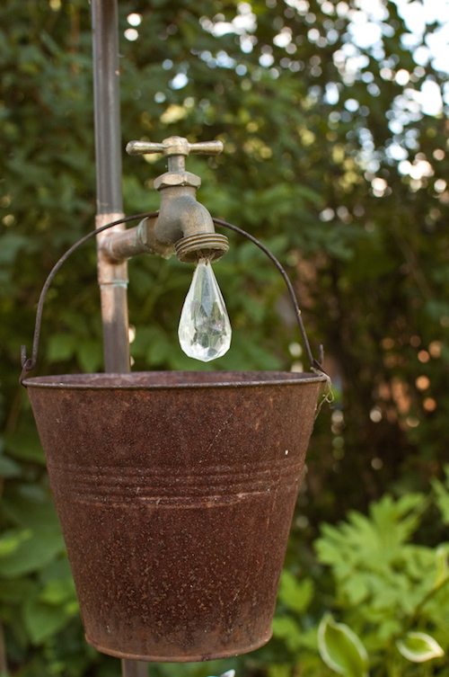 Add a pretty little crystal (found at a craft store) and a rusty bucket to create a beautiful outdoor water droplet decoration. So cute!
