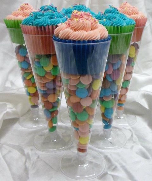 Use plastic champagne glasses from the $1 store and fill them with candy to make cupcake stands! Great idea!
