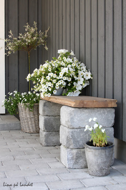 Use concrete pavers and wood to make a beautiful outdoor seat. It's just stunning with the white flowers!