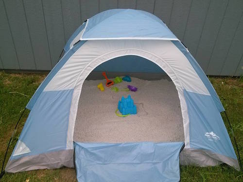Buy a kids tent and fill it with play sand. The kids can stay our of the hot sun and then you zip it up to keep animals and rain out. Win win!