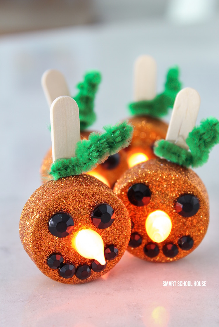 Tea Light Pumpkins - little orange flameless tea lights that stand up smile! Turn on the candle and the flame becomes the glowing pumpkin nose. They are ADORABLE and so easy to make!
