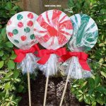 Giant paper plate lollipops for Christmas - Super cute as a garden Christmas decoration or line your driveway with them! They cost less than a dollar each to make!