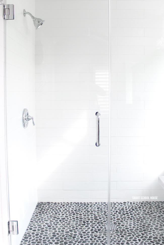 Gray and white bathroom ideas. Long white subway tiles. Large glass shower doors. Chrome fixtures. Spa-like rock flooring that warms up in the shower to comfort tired feet!