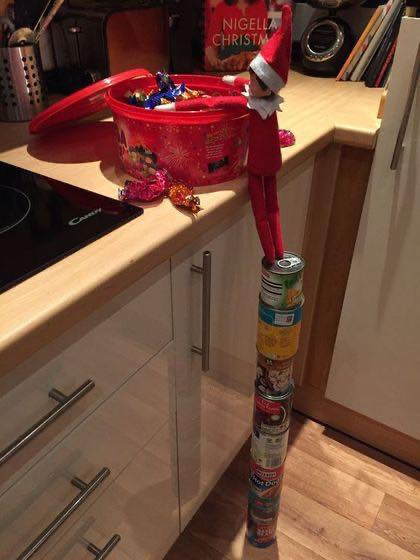 Elf on the Shelf Ideas:  Elf on a Stack of Cans Getting Into the Candy What a sneaky little elf! Source: Pinterest