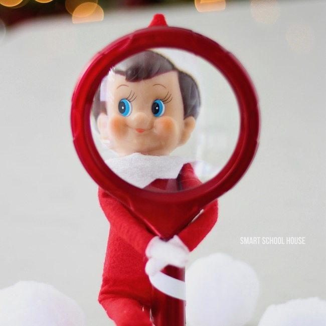 Elf on the Shelf looking through a Magnifying glass #ElfOnTheShelf #ElfOnTheShelfIdea #ElfOnTheShelfIdeas #EasyElfOnTheShelfIdea