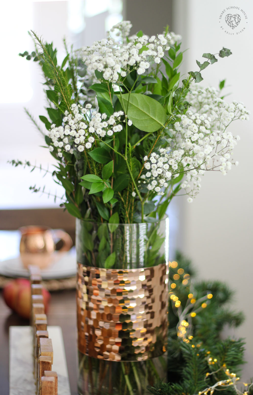 Copper and glass hurricane vase with eucalyptus, baby's breath, and string lights. #falldecor #falltablescape #homedecor