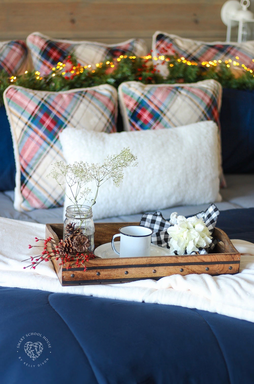 Cozy Holiday Bedding. Plaid pillows, garland, lanterns, and fairy lights.