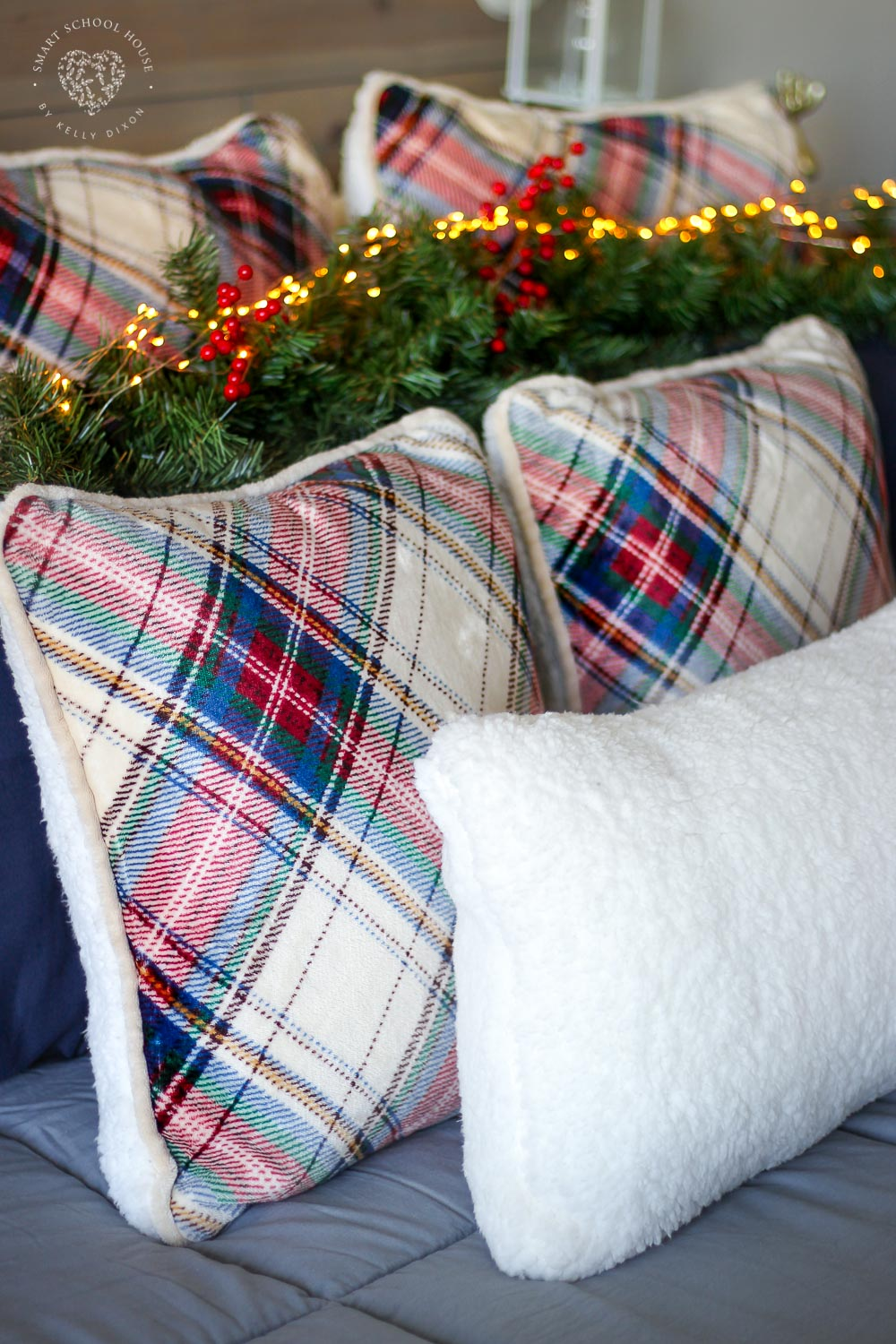 How to decorate a bed for the holidays. Plaid pillows, garland, lanterns, and fairy lights. Cozy Holiday Bedding.