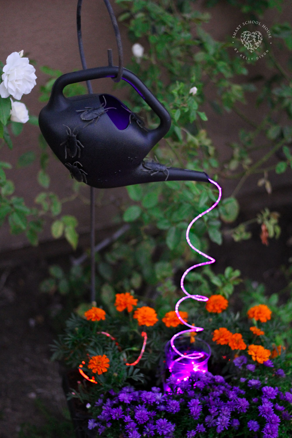 Halloween Watering Can with Lights. Spooky creepy crawlers on a black watering can with cascading purple lights.