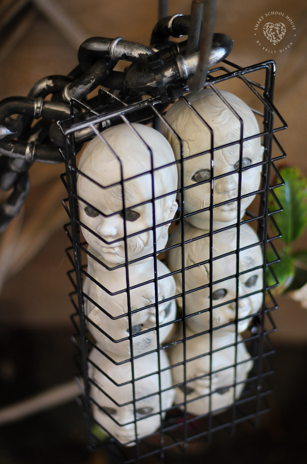 Hanging doll heads in a cage for Halloween!