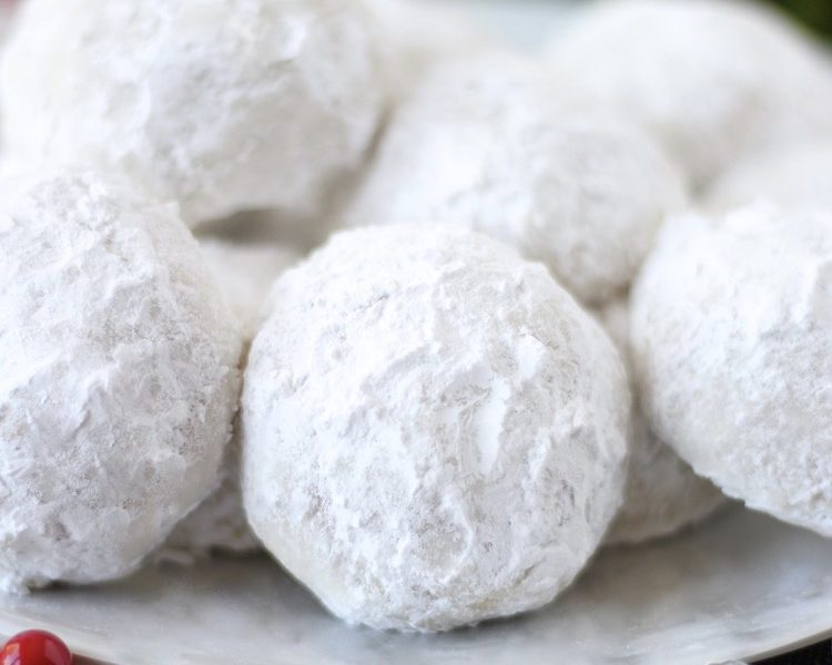 These traditional Snowball Cookies are a beautiful addition to your holiday cookie plates and dessert tables. They have a buttery vanilla flavor surrounded by soft and snowy powdered sugar. Snowball Cookies have a crumbly, buttery, nutty texture that just melts in your mouth and are completely irresistible. These holiday cookies are simply the BEST! Everyone loves this classic Christmas cookie recipe. Snowball Cookies These cookies are sometimes called Russian Tea Cakes or Mexican Wedding Cookies. Whatever you name them in your house, they are sure to be a hit (especially with kiddos in December!). They are special because they are delectable buttery, nutty, round shortbread cookies. We also love them so much because they are covered in powdered sugar that remind us of snowballs and playing in the snow.