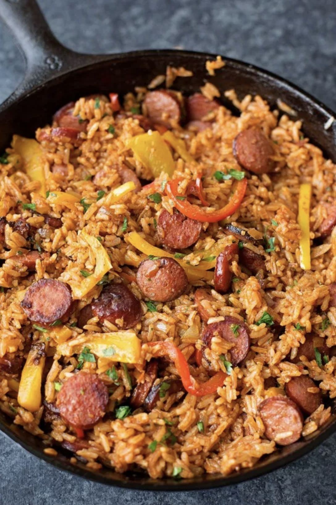 Sausage, Pepper, and Rice Skillet - Smoky kielbasa sizzled with sweet bell pepper, onions and garlic in vibrant tomato sauce. This quick and easy sausage, pepper and rice skillet is downright delicious!