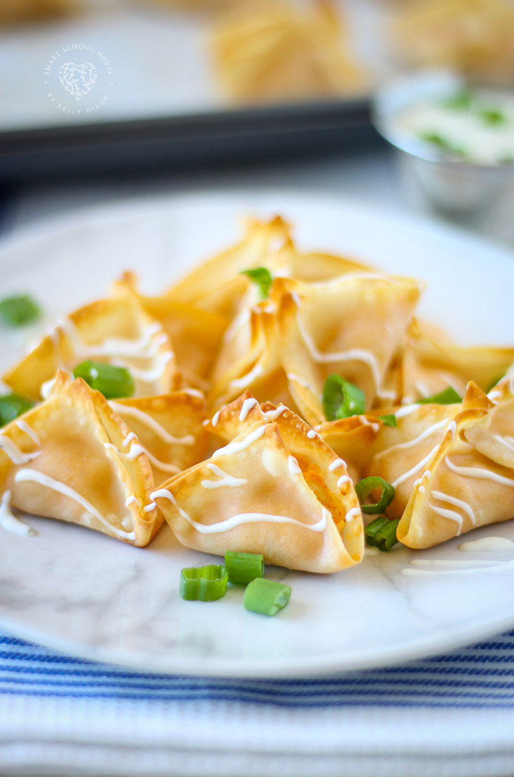 Buffalo Chicken Wontons. Baked, not fried! Creamy buffalo chicken drizzled in dressing! Done in 12 minutes.