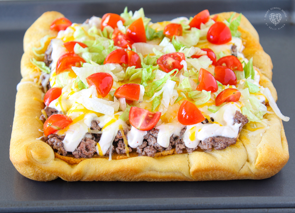 This 30 minute dinner turns fluffy crescent dough turned into pizza crust. The special cheese sauce in this Taco Pizza makes it OVER THE TOP!