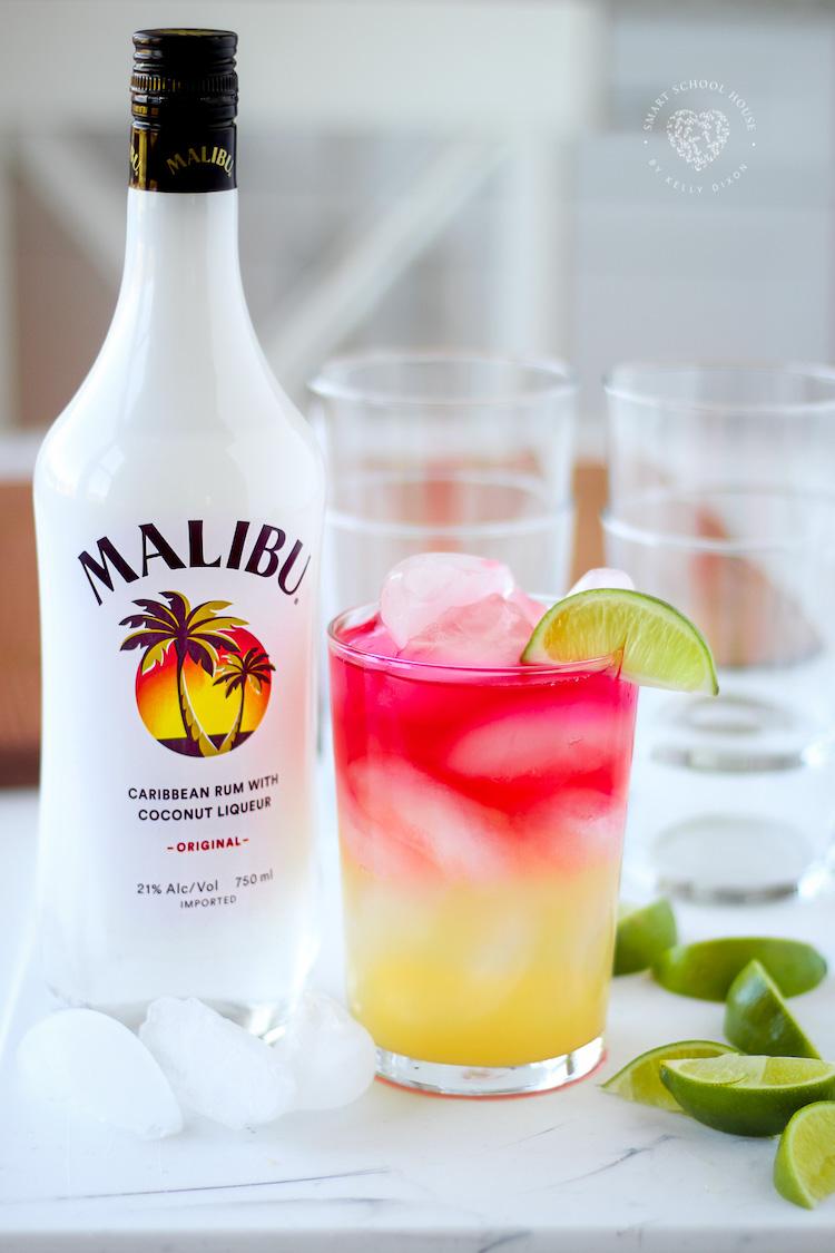 A bebida para desfrutar durante todo o verão!  Malibu Rum, suco de abacaxi e suco de cranberry com gelo e uma rodela de limão